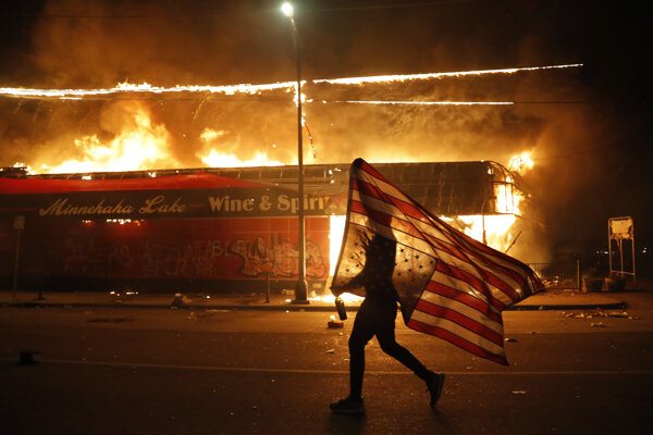Demonštrant nesie americkú vlajku vedľa horiacej budovy počas pokračujúcich protestov proti policajnému zásahu v americkom meste Minneapolis vo štvrtok 28. mája 2020.