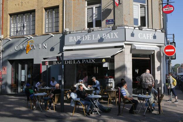Ľudia sedia na vonkajšej terase kaviarne počas jej znovuotvorenia v Lille.