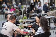 Ľudia sedia v kaviarni počas uvoľňovania opatrení v centre Bratislavy.