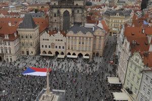 Ľudia stoja na značkách a dodržiavajú sociálny odstup počas protestu na Staromestskom námestí v Prahe.