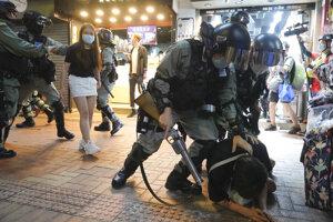 Príslušníci hongkongských poriadkových síl zatýkajú demonštranta počas protestu na Causeway Bay v Hongkongu 12. júna 2020.