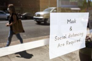 """Nápis """"Požadované sú rúška a sociálny odstup"""" visiaci na dverách kostola v meste Pullman v štáte Washington. Dôvodom sú opatrenia proti šíreniu koronavírusu."""
