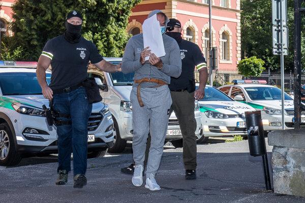 Norberta Bödöra privádzajú v putách na súd.