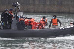 Záchranári eskortujú migrantov do prístavu v britskom Doveri.