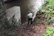 Policajt ukazuje miesto, kde našli zraneného muža.