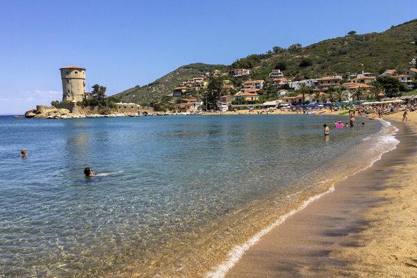 Ľudia na pláži na talianskom ostrove Giglio.