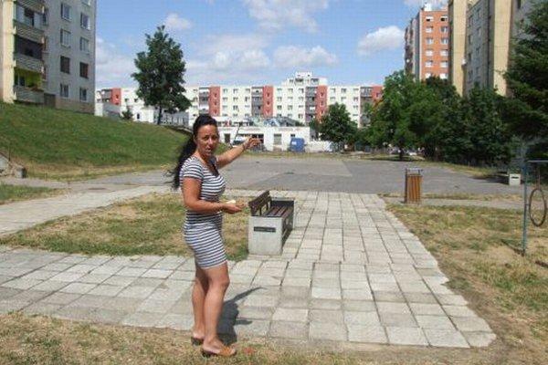 Petra Ajdariová stojí na ihrisku pred asfaltovou plochou, kde zvažuje mesto vytvoriť parkovisko. V pozadí je budova, v ktorej bude škôlka.