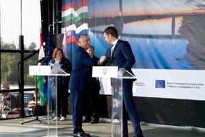Maďarský premiér Viktor Orbán (vľavo) a premiér SR Igor Matovič (vpravo) sa zdravia lakťami pri otvorení mosta Monoštor medzi mestami Komárno a Komárom.