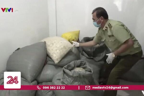 Na zábere zverejnenom televíznou stanicou VTV policajt berie vrece s použitými kondómami, ktoré priekupníci čistili a opätovne predávali ako nové v provincii Binh Duong na juhu Vietnamu 10. septembra 2020.