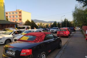 V priebehu niekoľkých minút sa pri škole vystriedajú desiatky áut.