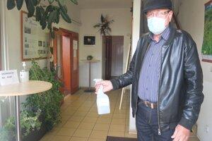 S dezinfekciou rúk pomáha voličom člen volebnej komisie.