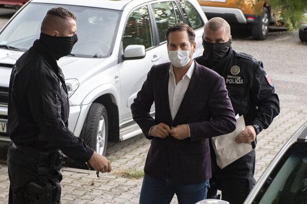 Uprostred starosta bratislavskej mestskej časti Nové Mesto Rudolf Kusý prichádza v sprievode polície na Okresný súd.