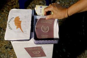 Demonštrantka si berie napodobeninu cyperského pasu počas demonštrácie proti korupcii pred konferenčným centrom v Nikózii 14. októbra 2020. Predseda cyperského parlamentu Dimitris Sylluris 15. októbra 2020 odstúpil zo svojej funkcie. Urobil tak po tom, ako vyšlo najavo, že je zapletený do škandálu s programom takzvaných zlatých víz, ktorý ponúkal cyperské občianstvo a bezvízový styk v celej EÚ výmenou za investíciu najmenej dvoch miliónov eur.