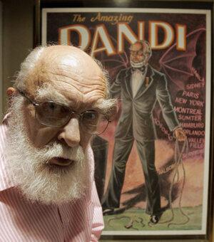 James Randi pózuje pred plágátom vo svojom dome.