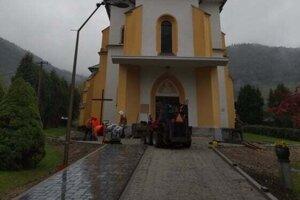 Pred kostolom kladú kamennú dlažbu.