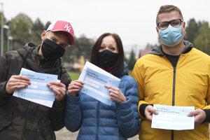 Otestovaní ukazujú svoju certifikáty v obci Zborov.