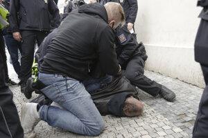Policajt zadržuje demonštranta počas protestu proti koronavírusovým opatreniam 28. októbra 2020 v Prahe.