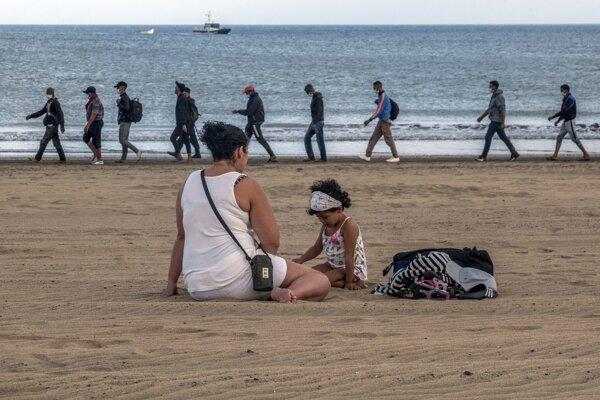 Migranti z Maroka kráčajú po pobreží na Kanárskych ostrovoch.