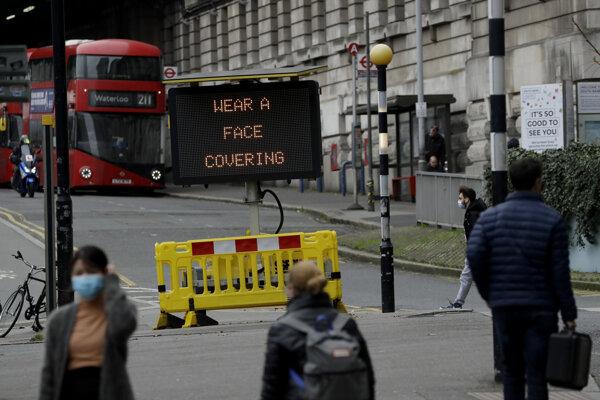 Tabuľa v Londýne upozorňuje ľudí, aby si nasadili rúška.