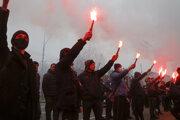 Ukrajinskí nacionalisti si pripomínajú obete hladomoru zažatými svetlicami pred ruskou ambasádou v Kyjeve.