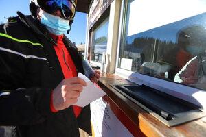 Lyžiar čaká pred pokladňou s negatívnym testom na ochorenie COVID-19  v lyžiarskom stredisku na Záhradišti na Donovaloch.