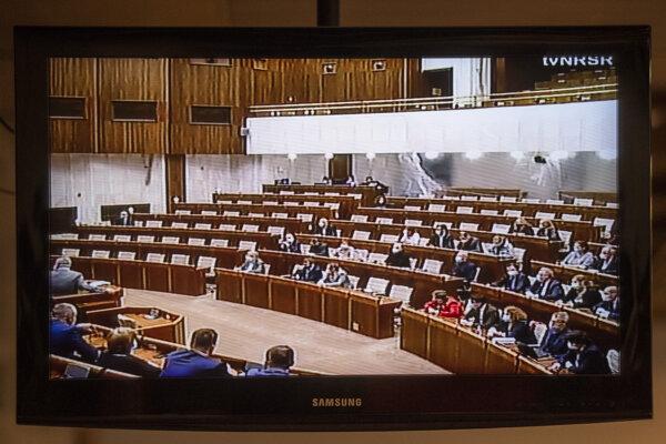 Fólie v rokovacej sále na obrazovke, ktorú sledujú novinári na prízemí Národnej rady počas mimoriadnej schôdze.