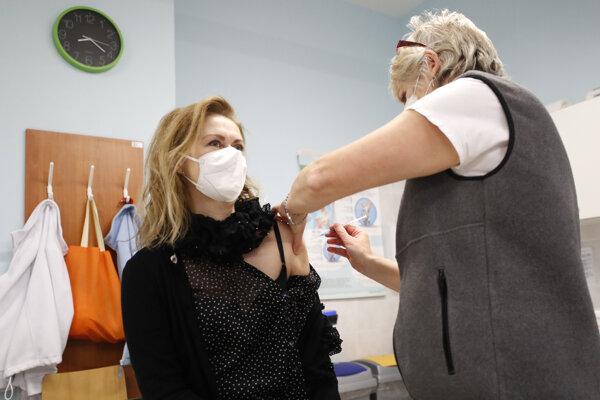 Pracovníčka vojenskej nemocnice v Prahe dostáva vakcínu proti ochoreniu COVID-19.