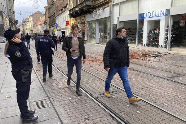 Obyvatelia Záhrebu prechádzajú okolo trosiek spôsobených zemetrasením v centre mesta.