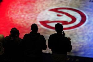 Fanúšikovia tímu Atlanta Hawks stoja pri hymne pred zápasom NBA proti Philadelphia 76ers.