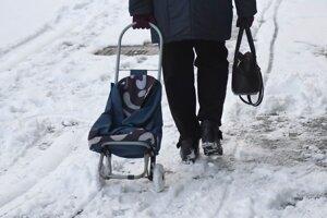 Seniorka kráča s vozíkom po zasneženej Hlavnej ulici v Košiciach.