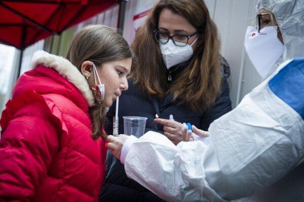 Dievča sa testuje počas PCR testu metódou odberu formou kloktania.