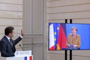Francúzsky prezident Emmanuel Macron máva na rozlúčku nemeckej kancelárke Angele Merkelovej na záver tlačovej konferencie po virtuálnom rokovaní nemecko-francúzskej rady pre obranu a bezpečnosť.