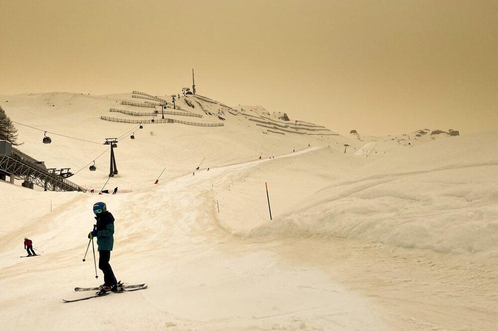 Lyžiar na svahu pokrytým snehom, ktorý je sfarbený saharským pieskom na oranžovo a vytvára špeciálnu svetelnú atmosféru vo švajčiarskom lyžiarskom stredisku Anzére.