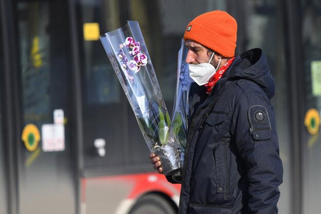 Cestujúci s respirátorom drží orchideu na zastávke na Sídlisku III v Prešove.
