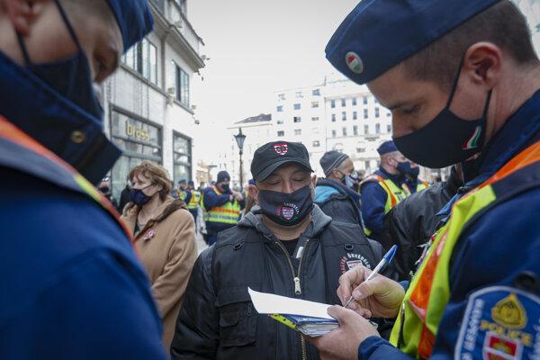 Policajt si zapisuje údaje muža počas protestu proti novým reštriktívnym opatreniam vlády.