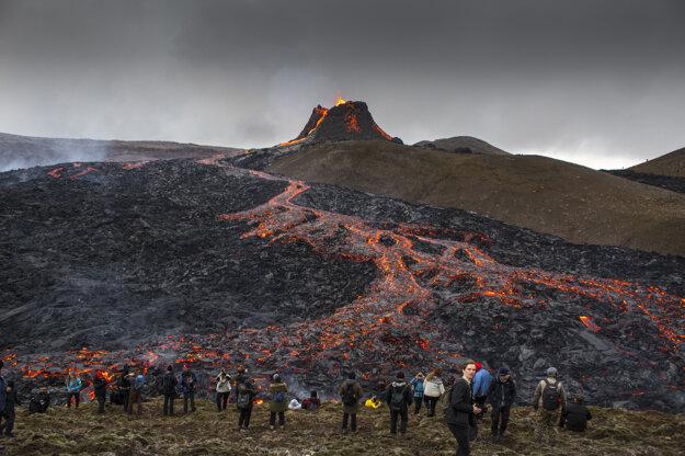 Ľudia sledujú vytekajúcu lávu počas erupcie sopky na polostrove Reykjanes  na juhozápade Islandu.