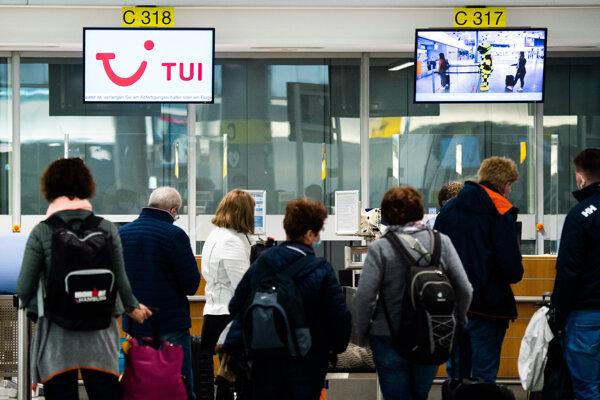 Cestujúci stoja na check-in na let Tuifly Flug X3 2146 do Palmy de Mallorca na letisku v Hannoveri.