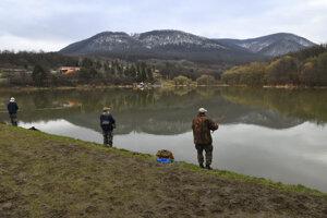 Hrádza Vodnej nádrže Sigord, v mapách tiež ako Vodná nádrž Kokošovce, obsadená rybármi na začiatku pstruhovej sezóny.