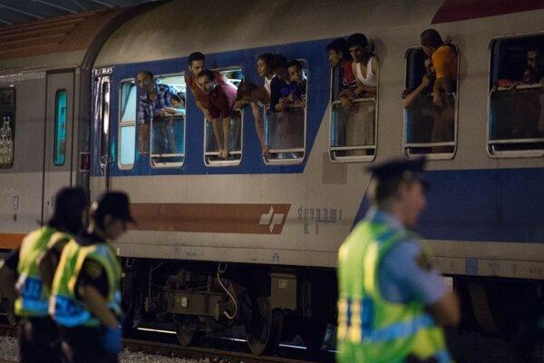 Migranti vyzerajú z okien počas kontroly vlaku smerujúceho z Chorvátska, ktorý zastavila slovinská polícia na železničnej stanici v slovinskej pohraničnej obci Dobova v piatok 18. septembra 2015.