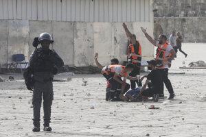 Palestínčania evakuujú zraneného muža počas násilnej potýčky medzi izraelskou políciou a Palestínčanmi.