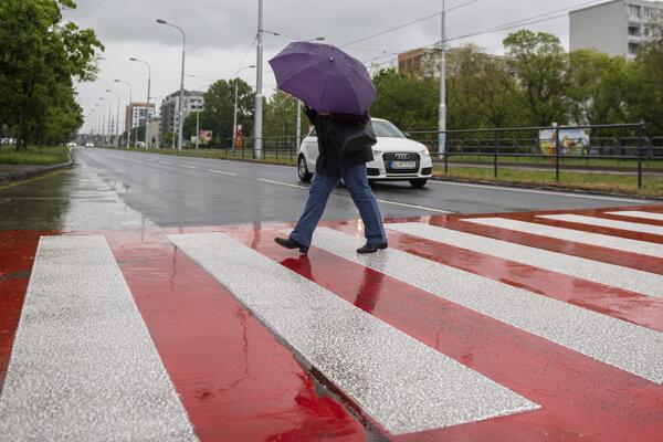 Žena s dáždnikom kráča cez priechod pre chodcov počas dažďa v bratislavskej mestskej časti Ružinov.
