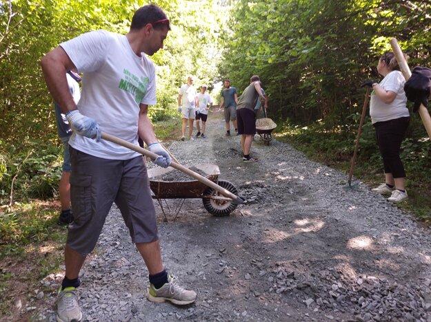 Dobrovoľníci pomáhajú upravovať chodník na hrad Šebeš.