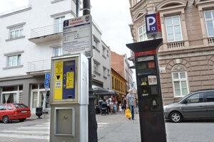 Symbol sporu - vedľa seba stojace funkčné parkomaty mesta (vľavo) a EEI.