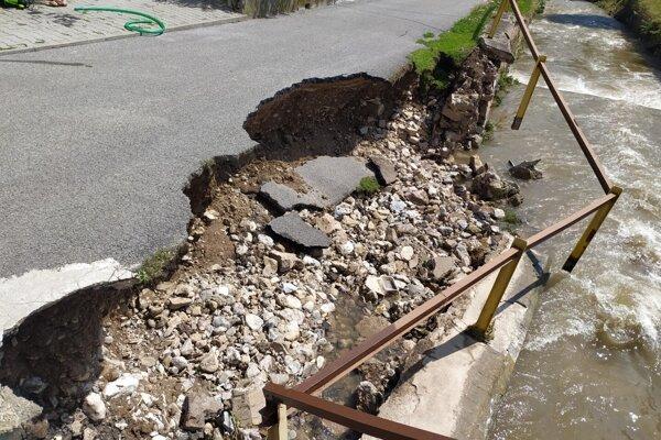 Do potoka sa zosunula časť miestnej cesty.