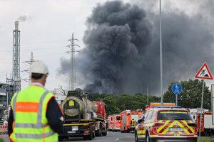 Hasičské autá stoja v blízkosti chemického závodu, v areáli ktorého došlo k mohutnej explózii v nemeckom meste Leverkusen.