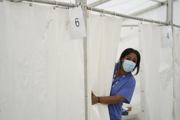 Zdravotná sestra privoláva ďalšieho človeka na očkovanie proti ochoreniu Covid-19. Británia patrí medzi najzaočkovanejšie krajiny sveta.