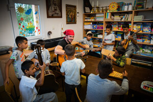 Skupinka chlapcov okolo hudobníka Andreja Klobušníka na hudobnom workshope.