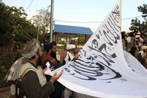 Bojovníci Talibanu sa modlia počas toho, ako vztyčujú svoju vlajku.
