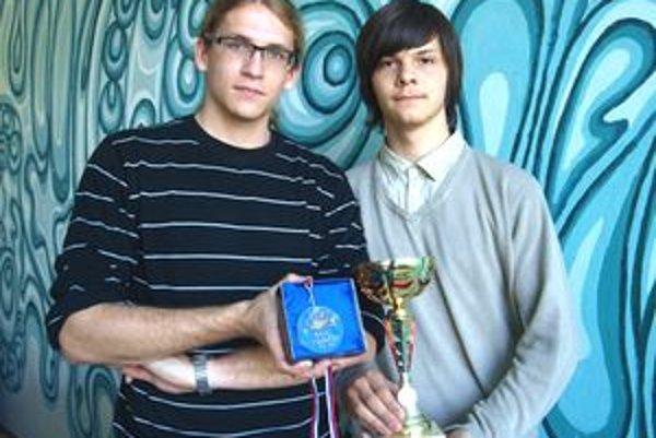 Zľava Matúš Baloh a Matúš Sitkey s pohárom a medailou pre víťazov. Vyhrali aj 30-eurovú poukážku na nákup elektroniky  kalkulačku, multimeter a tričko.