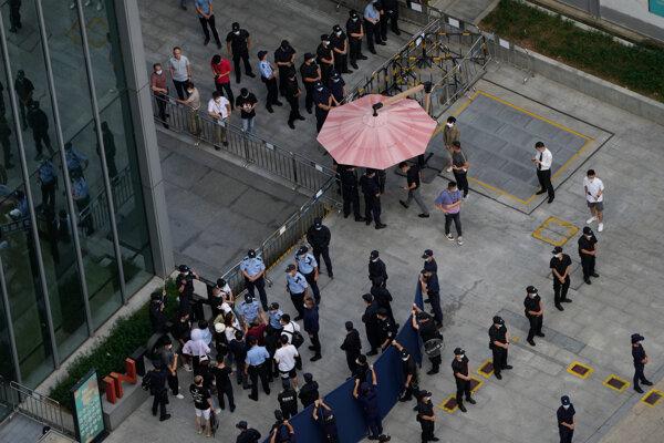 Investori sú obkľúčení políciou a bezpečnostným personálom, keď sa pokúšajú dostať do sídla Evergrande.